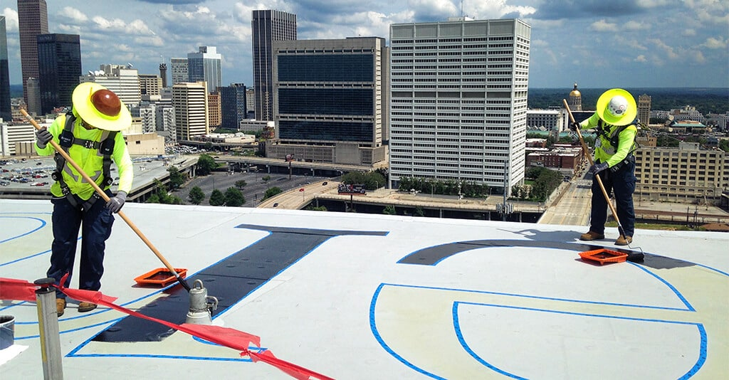 Roof Logo workers high atop the city of Atlanta painting on the logo of the Mercedes-Benz Stadium